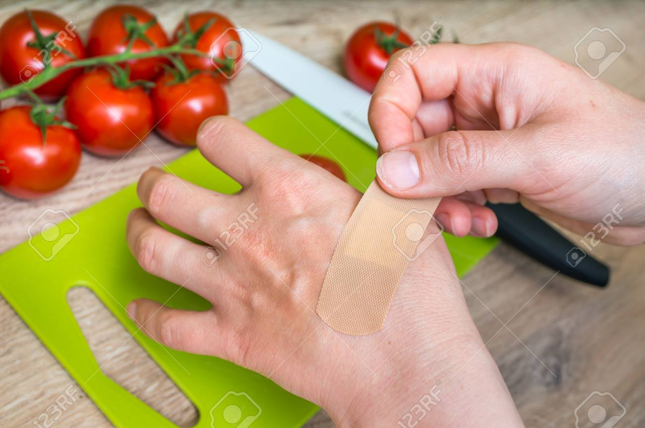 Woman apply plaster on her hand - injury in kitchen