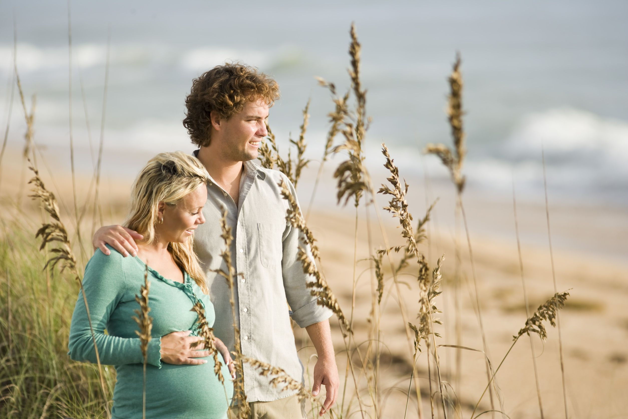 6683601 - happy young pregnant woman at beach with husband